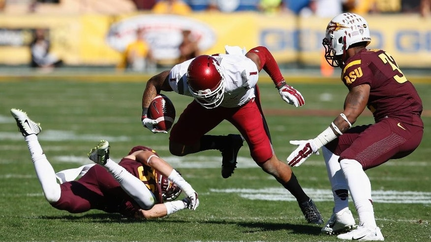 Washington State's Vince Mayle (1) slips past Arizona State's Jordan Simone, left, as Arizona State's Antonio Longino (32) moves in to make the tackle during the first half of an NCAA college football game Saturday, Nov. 22, 2014, in Tempe, Ariz. (AP Photo/Ross D. Franklin)