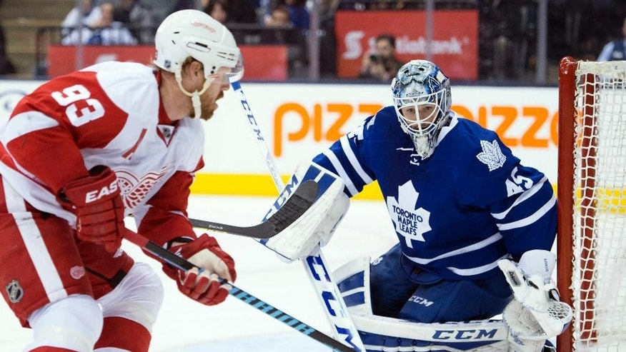 Toronto Maple Leafs goaltender Jonathan Bernier defends against Detroit Red Wings' Johan Franzen (93) as he chases the puck during the third period of an NHL hockey game in Toronto on Saturday, Nov. 22, 2014. (AP Photo/The Canadian Press, Frank Gunn)