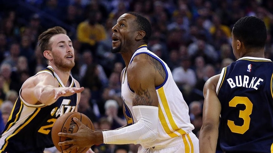 Golden State Warriors' Andre Iguodala, center, drives the ball between Utah Jazz forward Gordon Hayward, left, and Trey Burke (3) during the second half of an NBA basketball game Friday, Nov. 21, 2014, in Oakland, Calif. (AP Photo/Ben Margot)