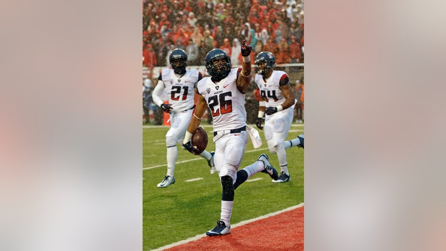 Arizona safety Jourdon Grandon (26) celebrates after his interception in the second quarter during an NCAA college football game against Utah, Saturday, Nov. 22, 2014, in Salt Lake City. (AP Photo/Rick Bowmer)