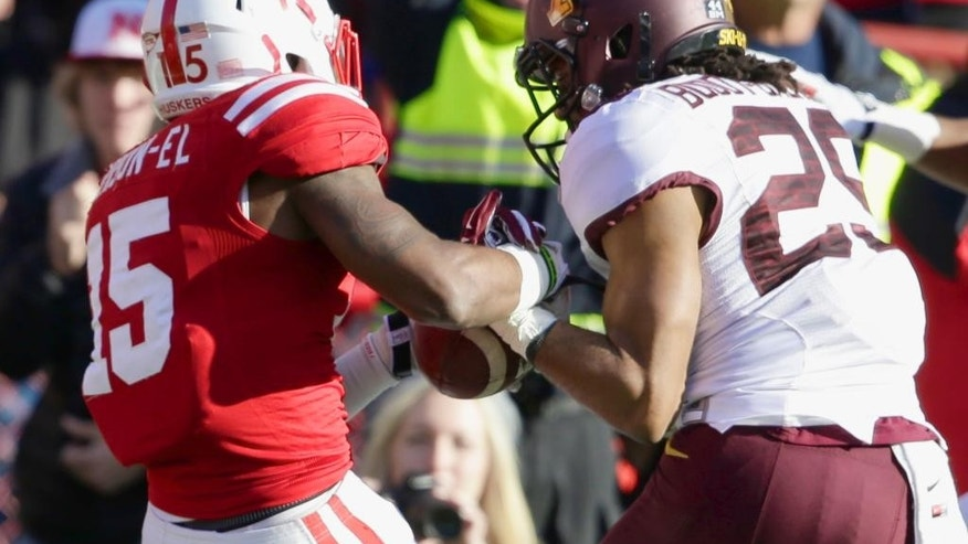 Briean Boddy-Calhoun, right, rips the ball out of the hands of Nebraska receiver De'Mornay Pierson-El's hands (15) during the fourth quarter of an NCAA college football game in Lincoln, Neb., Saturday, Nov. 22, 2014. Minnesota won 28-24. (AP Photo/Nati Harnik)