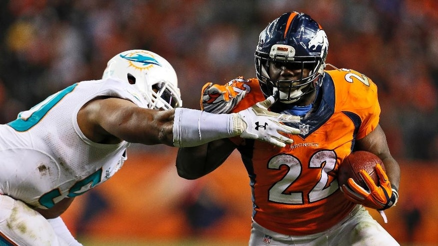 Denver Broncos running back C.J. Anderson (22) runs as Miami Dolphins defensive end Olivier Vernon defends during the second half of an NFL football game, Sunday, Nov. 23, 2014, in Denver. (AP Photo/Joe Mahoney)