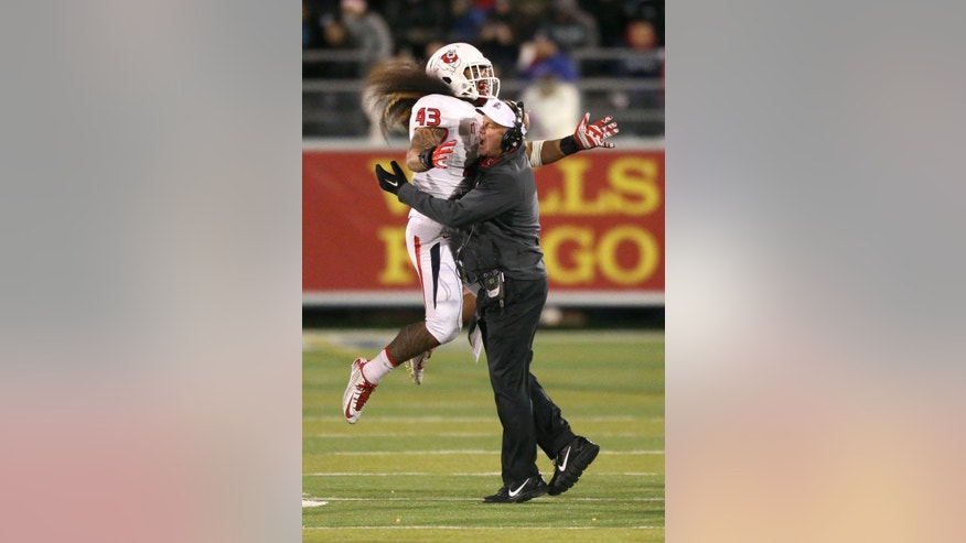 Fresno State's Karl Mickelsen (43) celebrates with coach Tim DeRuyter after a defensive play against Nevada during the first half of an NCAA college football game in Reno, Nev., on Saturday, Nov. 22, 2014. (AP Photo/Cathleen Allison)