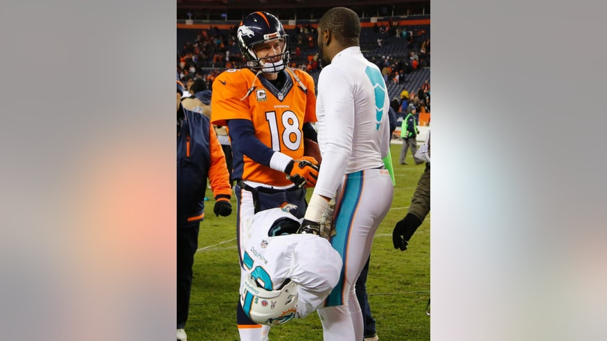 Denver Broncos quarterback Peyton Manning (18) greets Miami Dolphins linebacker Chris McCain after an NFL football game, Sunday, Nov. 23, 2014, in Denver. The Broncos won 39-36. (AP Photo/Jack Dempsey)
