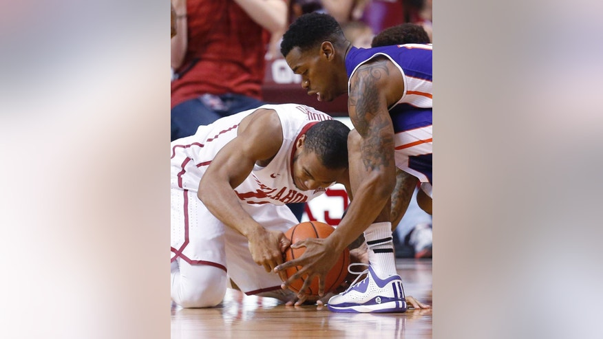 Oklahoma guard Jordan Woodard, left, and Northwestern State guard Jalan West, right, reach for the ball in the first half of an NCAA college basketball game in Norman, Okla., Sunday, Nov. 23, 2014. (AP Photo/Sue Ogrocki)