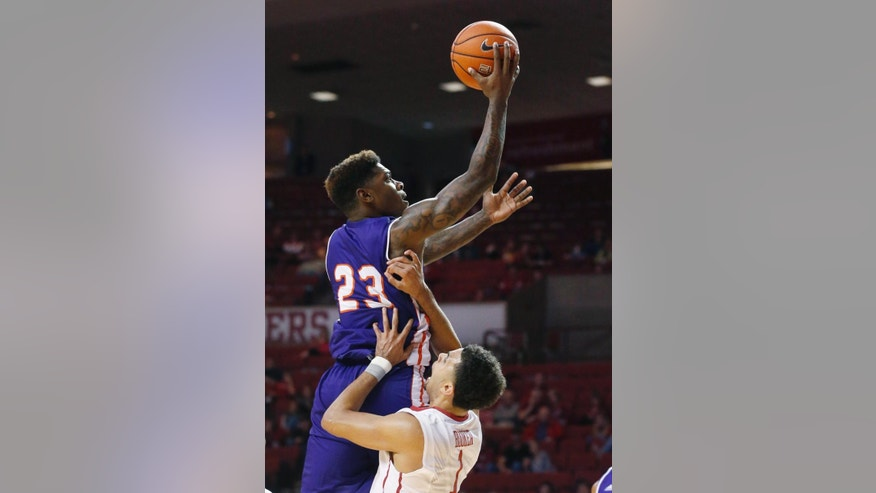Northwestern State guard Zeek Woodley (23) is fouled by Oklahoma guard Frank Booker (1) while shooting in the first half of an NCAA college basketball game in Norman, Okla., Sunday, Nov. 23, 2014. (AP Photo/Sue Ogrocki)