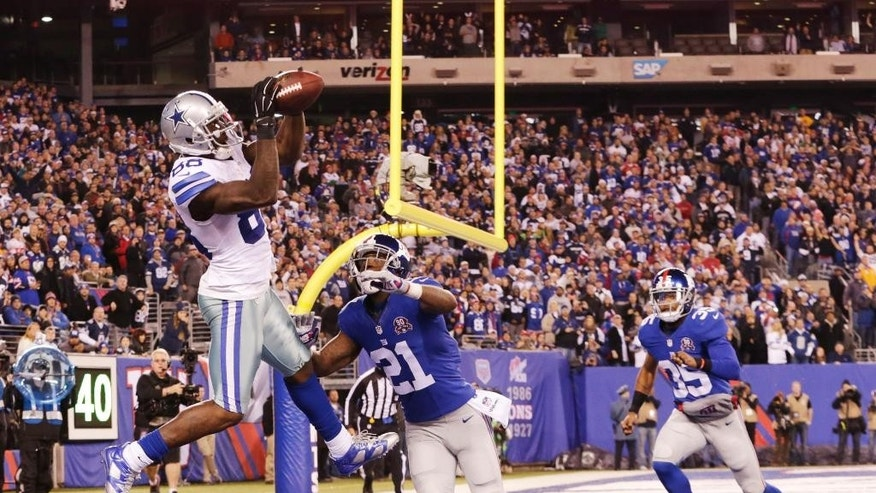 Dallas Cowboys wide receiver Dez Bryant (88) catches a pass for a touchdown against New York Giants cornerback Dominique Rodgers-Cromartie (21) in the fourth quarter of an NFL football game, Sunday, Nov. 23, 2014, in East Rutherford, N.J. (AP Photo/Julio Cortez)