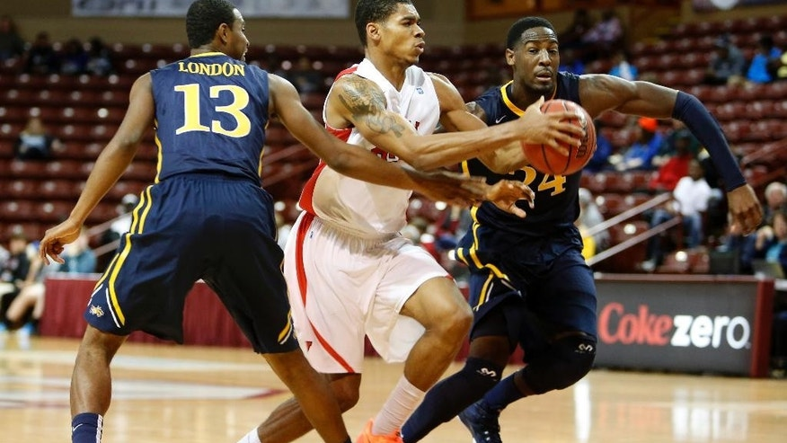 Cornell's Shonn Miller, center, drives through the defense of Drexel's Rashann London, left, and Rodney Williams, right in the first half at the Charleston Classic NCAA college basketball tournament in Charleston, S.C., Sunday, Nov. 23, 2014. (AP Photo/Mic Smith)