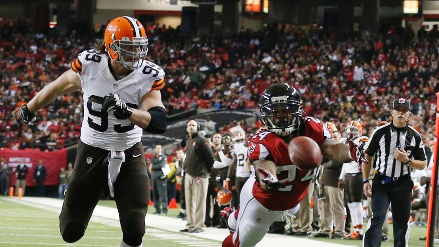 Atlanta Falcons running back Devonta Freeman (24) can't make the catch as Cleveland Browns outside linebacker Paul Kruger (99) looks on during the first half of an NFL football game, Sunday, Nov. 23, 2014, in Atlanta. (AP Photo/Brynn Anderson)