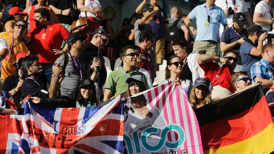 Spectators hold Great Britain and Germany flags are seen in front of supporters of Mercedes drivers Lewis Hamilton of Britain and Nico Rosberg of Germany in the main grand stand just before the start of Abu Dhabi Formula One Grand Prix at the Yas Marina racetrack in Abu Dhabi, United Arab Emirates, Sunday, Nov. 23, 2014. (AP Photo/Hassan Ammar)