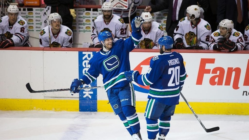 Vancouver Canucks' Jannik Hansen, left, of Denmark, and Chris Higgins celebrate Hansen's third goal against the Chicago Blackhawks during the third period of an NHL hockey game in Vancouver, British Columbia on Sunday, Nov. 23, 2014. (AP Photo/The Canadian Press, Darryl Dyck)