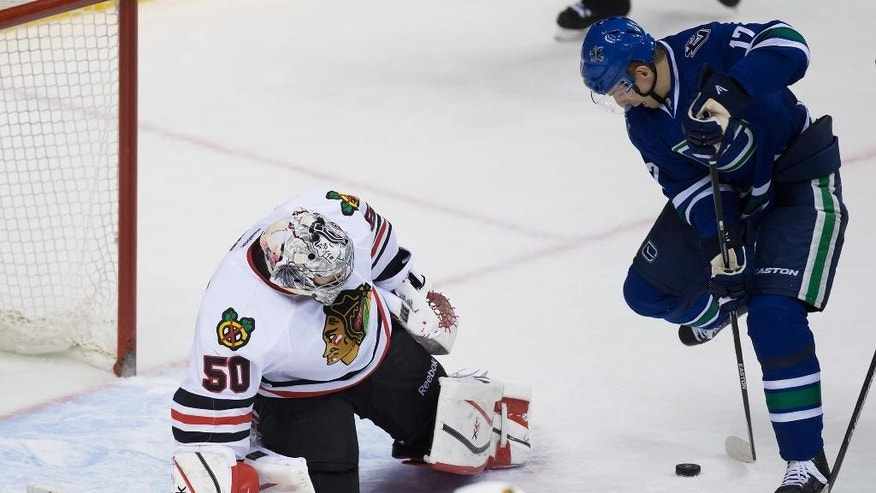 Vancouver Canucks' Radim Vrbata, right, of the Czech Republic, scores against Chicago Blackhawks' goalie Corey Crawford during the third period of an NHL hockey game in Vancouver, British Columbia on Sunday, Nov. 23, 2014. (AP Photo/The Canadian Press, Darryl Dyck)
