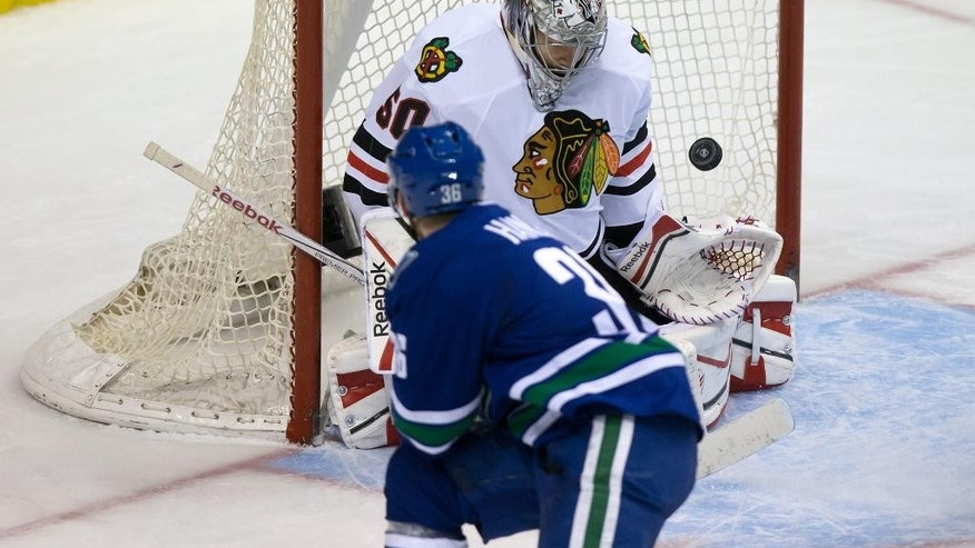 Vancouver Canucks' Jannik Hansen, bottom, of Denmark, scores his second goal against Chicago Blackhawks' goalie Corey Crawford during the third period of an NHL hockey game in Vancouver, British Columbia on Sunday, Nov. 23, 2014. (AP Photo/The Canadian Press, Darryl Dyck)