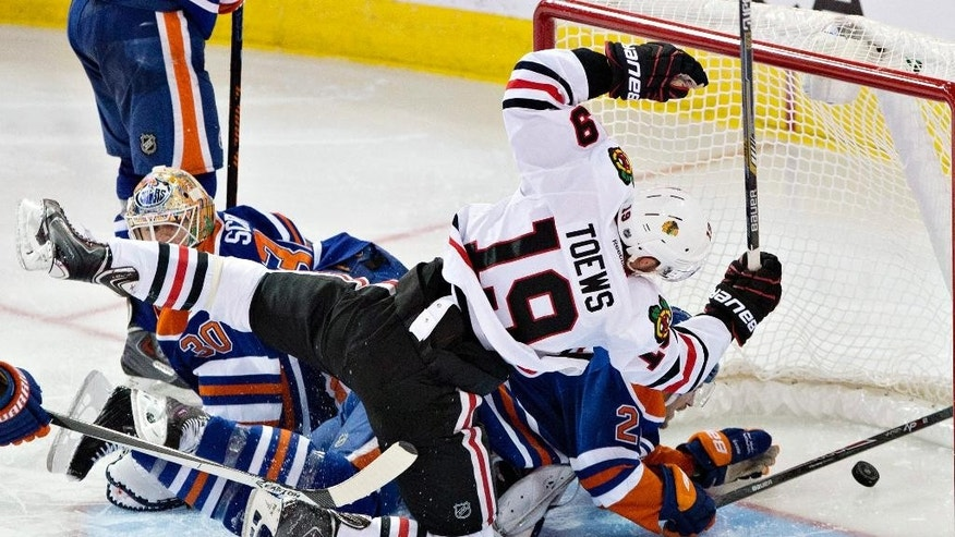 Chicago Blackhawks' Jonathan Toews (19) scores a goal on Edmonton Oilers goalie Ben Scrivens (30) during the second period of an NHL hockey game Saturday, Nov. 22, 2014, in Edmonton, Alberta. (AP Photo/The Canadian Press, Jason Franson)
