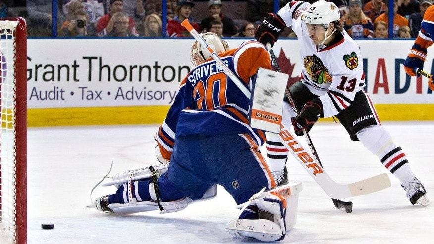 Chicago Blackhawks' Daniel Carcillo (13) is stopped by Edmonton Oilers goalie Ben Scrivens (30) during the first period of an NHL hockey game Saturday, Nov. 22, 2014, in Edmonton, Alberta. (AP Photo/The Canadian Press, Jason Franson)