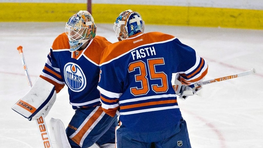 Edmonton Oilers goalie Ben Scrivens (30) and goalie Viktor Fasth (35) pass each other after Scrivens was pulled from the net against the Chicago Blackhawks during the second period of an NHL hockey game Saturday, Nov. 22, 2014, in Edmonton, Alberta. (AP Photo/The Canadian Press, Jason Franson)