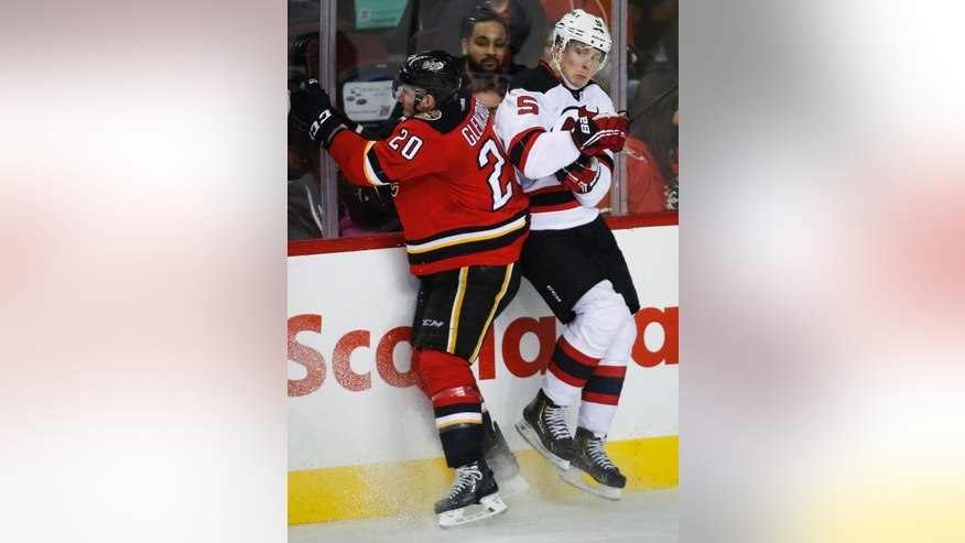New Jersey Devils' Adam Larsson, right, from Sweden, checks Calgary Flames' Curtis Glencross during second period NHL hockey action in Calgary, Alberta, Saturday, Nov. 22, 2014. (AP Photo/The Canadian Press, Jeff McIntosh)