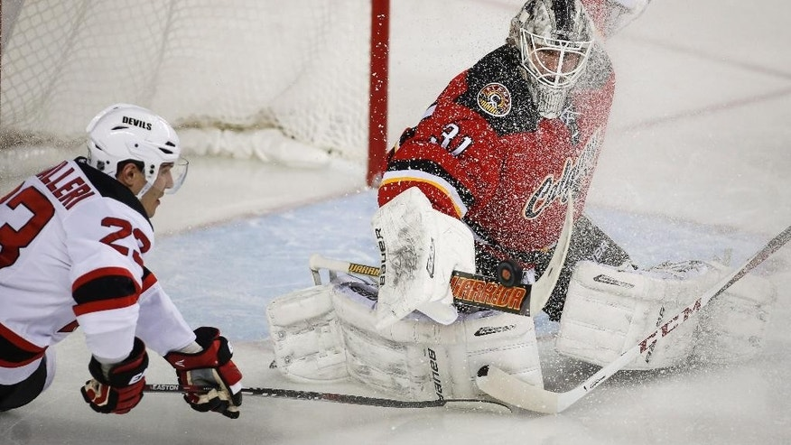 New Jersey Devils' Mike Cammalleri, left, looks on as Calgary Flames goalie Karri Ramo, from Finland, swats away his shot during second period NHL hockey action in Calgary, Alberta, Saturday, Nov. 22, 2014. (AP Photo/The Canadian Press, Jeff McIntosh)
