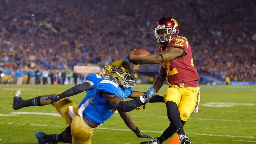 Southern California running back Justin Davis, right, scores a touchdown as UCLA defensive back Tahaan Goodman, center, and Ishmael Adams defend during the first half of an NCAA college football game, Saturday, Nov. 22, 2014, in Pasadena, Calif. (AP Photo/Mark J. Terrill)