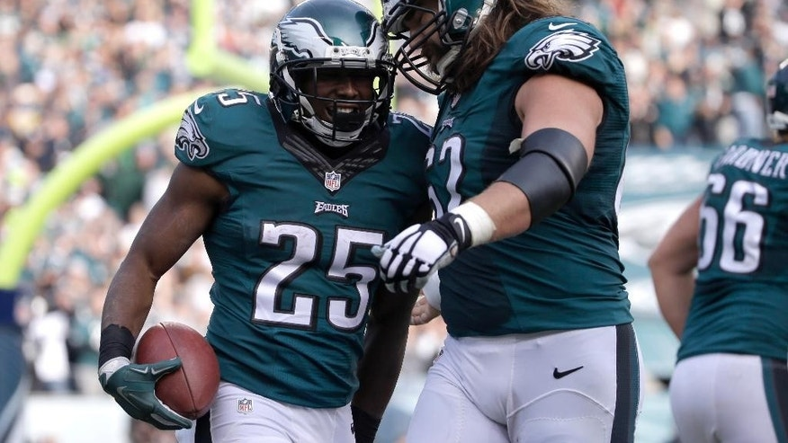 Philadelphia Eagles' LeSean McCoy, left, celebrates with Jason Kelce after McCoy's touchdown during the first half of an NFL football game against the Tennessee Titans, Sunday, Nov. 23, 2014, in Philadelphia. (AP Photo/Michael Perez)