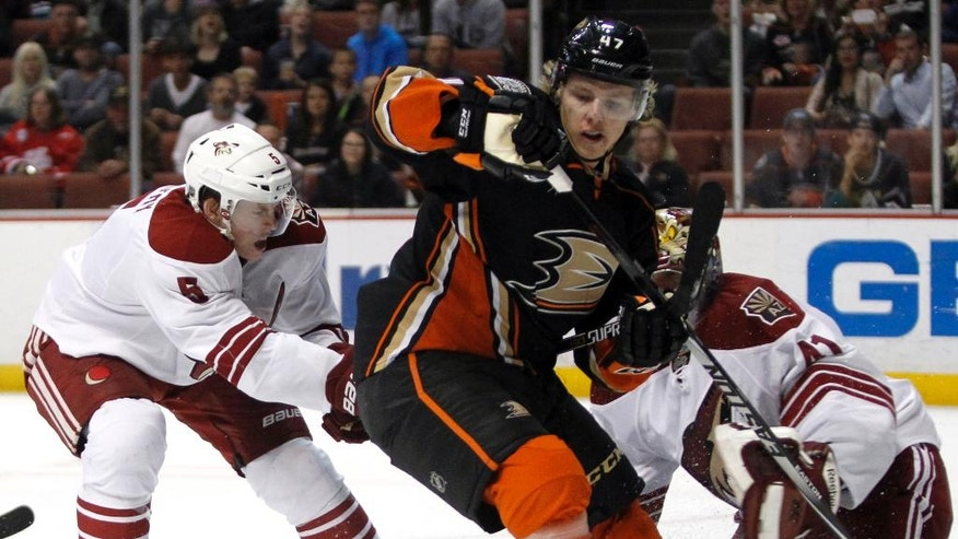 Anaheim Ducks defenseman Hampus Lindholm (47), of Sweden, watches the puck as Arizona Coyotes defenseman Connor Murphy (5) and goalie Mike Smith (41) defend during the second period of an NHL hockey game in Anaheim, Calif., Sunday, Nov. 23, 2014. (AP Photo/Alex Gallardo)