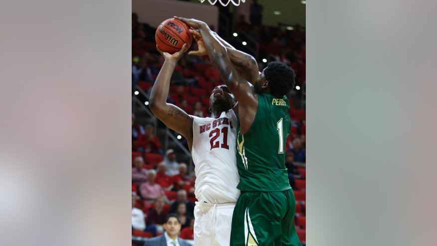 North Carolina State's Beejay Anya (21) shoots while defended by South Florida's Chris Perry (1) during the first half of an NCAA college basketball game in Raleigh, N.C., Sunday, Nov. 23, 2014. (AP Photo/The News & Observer, Ethan Hyman)  MANDATORY CREDIT