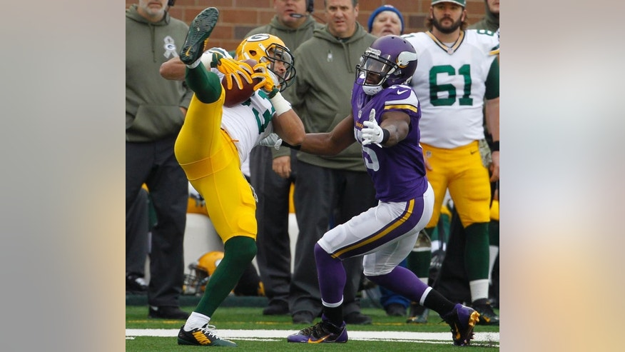 Green Bay Packers free safety Micah Hyde, left, intercepts a pass in front of Minnesota Vikings wide receiver Greg Jennings, right, during the first half of an NFL football game, Sunday, Nov. 23, 2014, in Minneapolis. (AP Photo/Ann Heisenfelt)