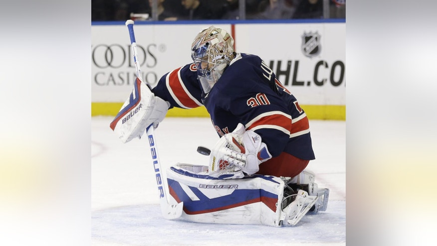New York Rangers goalie Henrik Lundqvist of Sweden blocks a shot during the first period of the NHL hockey game against the Montreal Canadiens, Sunday, Nov. 23, 2014, in New York. (AP Photo/Seth Wenig)