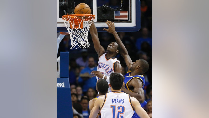 Oklahoma City Thunder guard Reggie Jackson (15) dunks in front of Golden State Warriors center Festus Ezeli (31) in the second quarter of an NBA basketball game in Oklahoma City, Sunday, Nov. 23, 2014. (AP Photo/Sue Ogrocki)