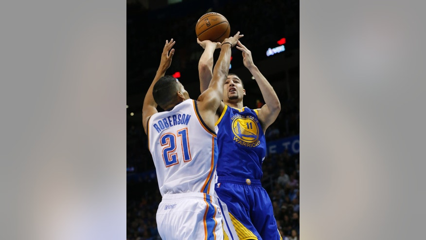 Golden State Warriors guard Klay Thompson (11) shoots as Oklahoma City Thunder guard Andre Roberson (21) defends in the first quarter of an NBA basketball game in Oklahoma City, Sunday, Nov. 23, 2014. (AP Photo/Sue Ogrocki)