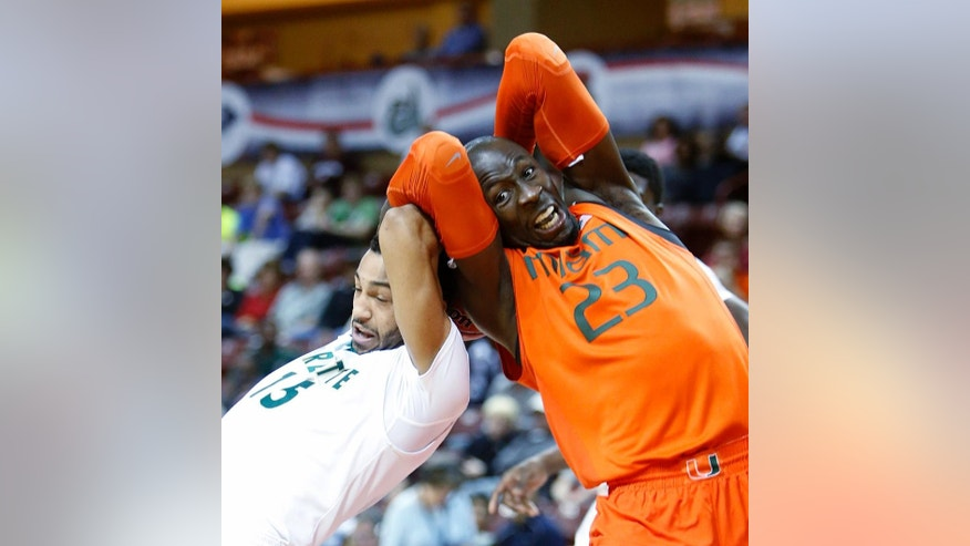 Miami's Tonye Jekiri, right, fights for a rebound against Charlotte's Pierria Henry, left, in the first half of the championship game at the Charleston Classic NCAA college basketball tournament in Charleston, S.C., Sunday, Nov. 23, 2014. (AP Photo/Mic Smith)