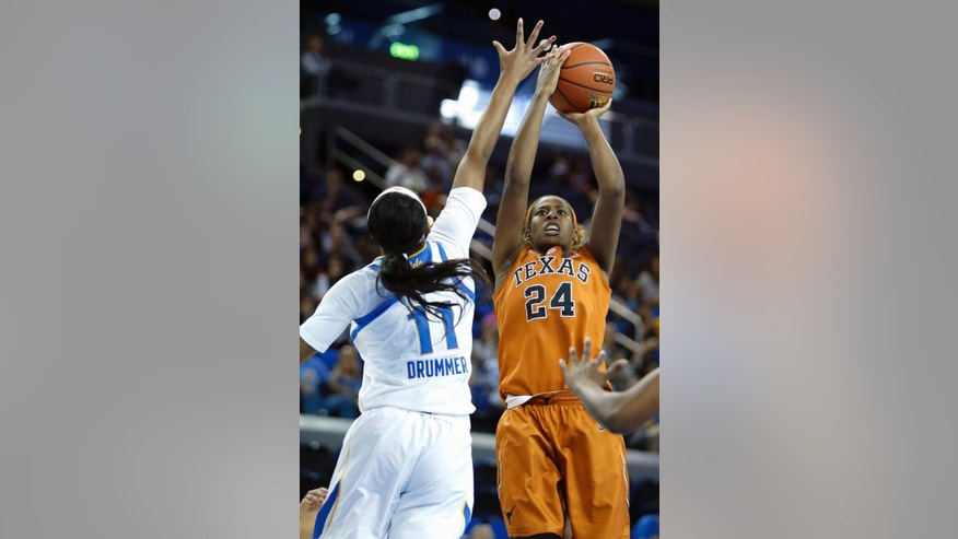 Texas guard Ariel Atkins (24) is fouled by UCLA forward Lajahna Drummer (11) in the first half of an NCAA college basketball game in Los Angeles, Sunday, Nov. 23, 2014. (AP Photo/Christine Cotter)