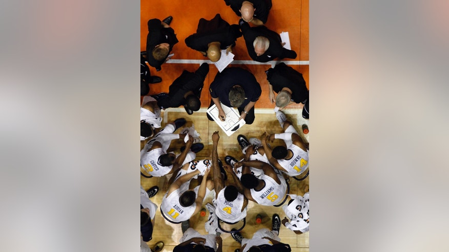 West Virginia basketball coach Bob Huggins, center, give instructions to his players during a time out at a NCAA college basketball game against UConn in San Juan, Puerto Rico, Sunday, Nov. 23, 2014. (AP Photo/Ricardo Arduengo)