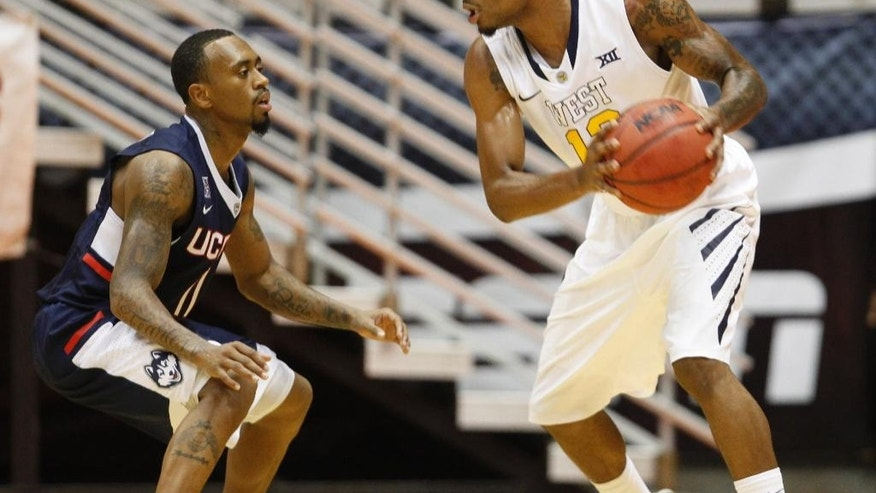 UConn guard Ryan Boatright, left, pressures West Virginia guard Terrence Phillip during a NCAA college basketball game in San Juan, Puerto Rico, Sunday, Nov. 23, 2014. (AP Photo/Ricardo Arduengo)