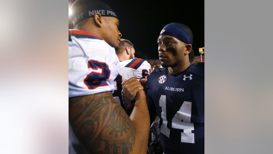 Samford quarterback Michael Eubank (2) shakes hands with Auburn quarterback Nick Marshall (14) after an NCAA college football game on Saturday, Nov. 22, 2014, in Auburn, Ala. Auburn defeated Samford 31-7. (AP Photo/Butch Dill)