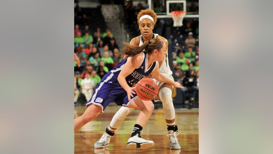 Holy Cross guard Lisa Mifsud, front, drives around Notre Dame forward Brianna Turner in the first half of an NCAA college basketball game, Sunday, Nov. 23, 2014, in South Bend, Ind. (AP Photo/Joe Raymond)