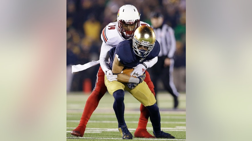 Louisville cornerback Terell Floyd (19) tackles Notre Dame wide receiver Will Fuller during the second half of an NCAA college football game in South Bend, Ind., Saturday, Nov. 22, 2014. Louisville won 31-28. (AP Photo/Nam Y. Huh)