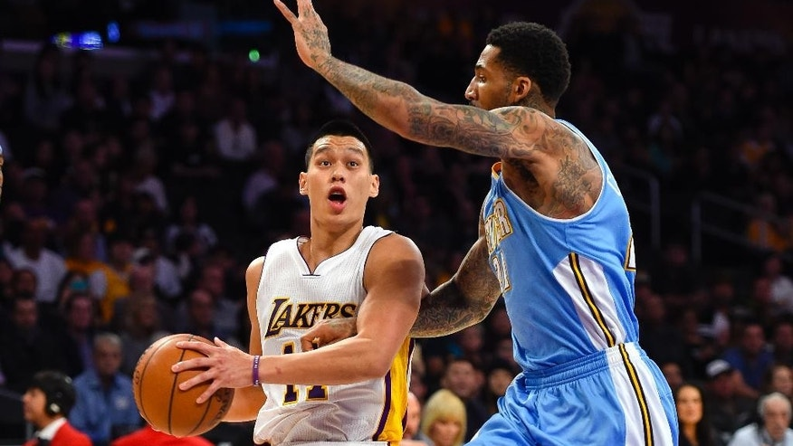 Los Angeles Lakers guard Jeremy Lin, left, drives on Denver Nuggets forward Wilson Chandler, right, in the first half of an NBA basketball game, Sunday, Nov. 23, 2014, in Los Angeles. (AP Photo/Gus Ruelas)