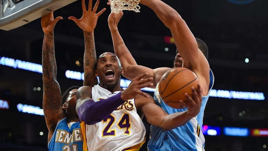 Los Angeles Lakers guard Kobe Bryant, center, gets double teamed by Denver Nuggets forward Wilson Chandler (21) and center JaVale McGee, right, as he drives to the basket in the first half of an NBA basketball game, Sunday, Nov. 23, 2014, in Los Angeles. (AP Photo/Gus Ruelas)