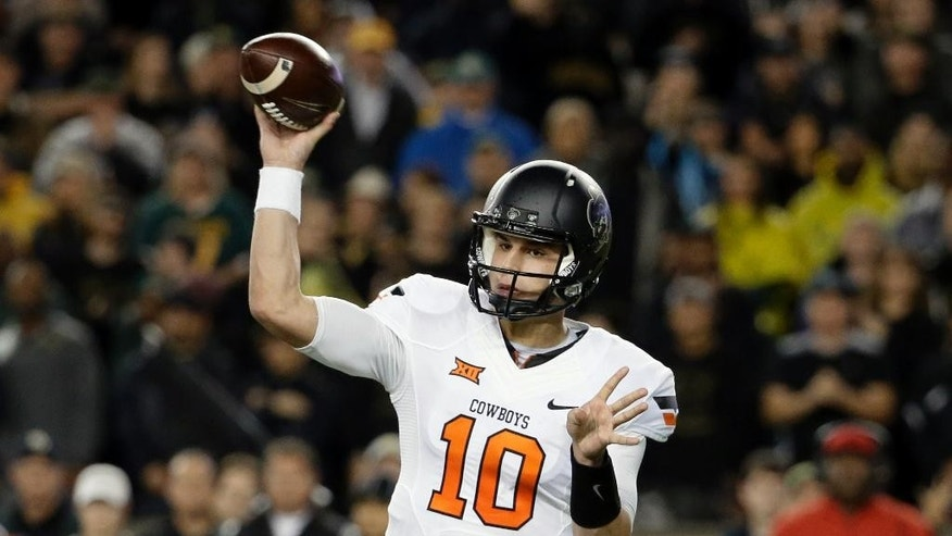 Oklahoma State quarterback Mason Rudolph (10) passes in the first half of an NCAA college football game against Baylor, Saturday, Nov. 22, 2014, in Waco, Texas. (AP Photo/Tony Gutierrez)