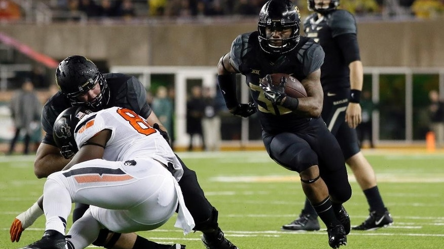 Baylor running back Shock Linwood (32) finds the gap as he gains yardage on a run in the first half of an NCAA college football game against Oklahoma State, Saturday, Nov. 22, 2014, in Waco, Texas. (AP Photo/Tony Gutierrez)