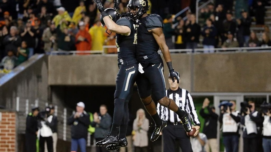 Baylor running back Clay Fuller, left, celebrates with wide receiver Jay Lee after Lee scored a touchdown on a long pass and run in the first half of an NCAA college football game against Oklahoma State, Saturday, Nov. 22, 2014, in Waco, Texas. (AP Photo/Tony Gutierrez)