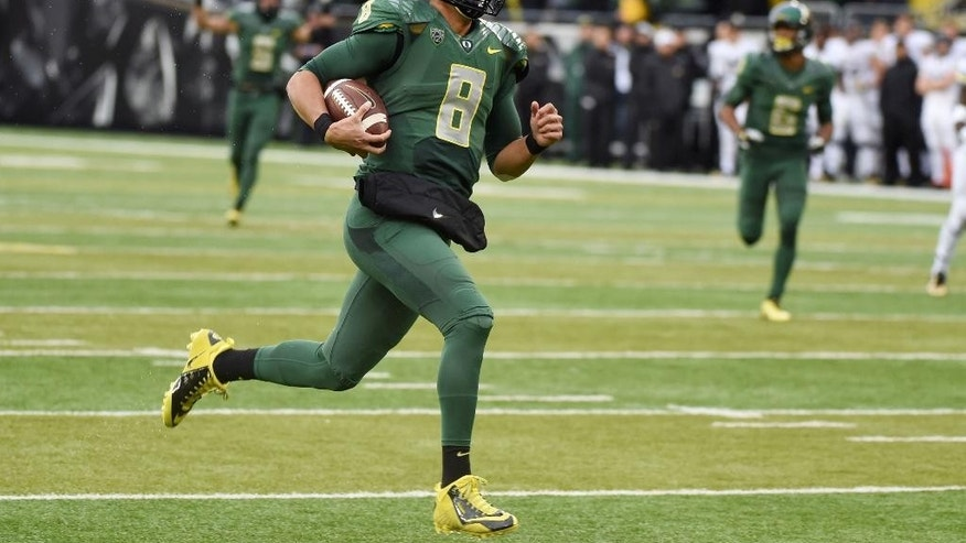 Oregon quarterback Marcus Mariota (8) runs in for a touchdown during the first quarter of an NCAA college football game against the Colorado on Saturday, Nov. 22, 2014, in Eugene, Ore. (AP Photo/Steve Dykes)