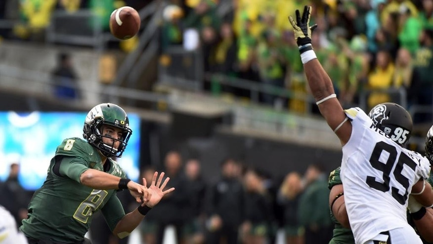 Oregon quarterback Marcus Mariota (8) passes the ball as Colorado defensive end Derek McCartney (95) applies pressure during the third quarter of an NCAA college football game on Saturday, Nov. 22, 2014, in Eugene, Ore. (AP Photo/Steve Dykes)