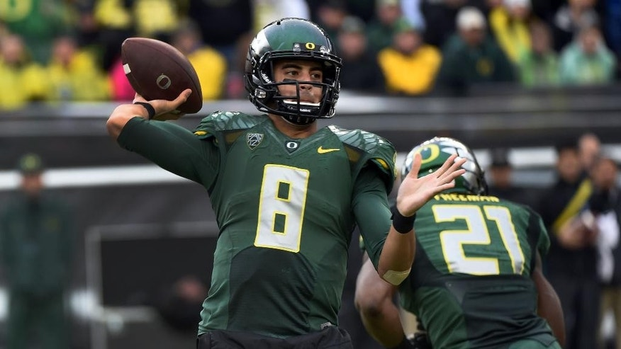 Oregon quarterback Marcus Mariota (8) passes the ball during the second quarter of an NCAA college football game against the Colorado on Saturday, Nov. 22, 2014, in Eugene, Ore. (AP Photo/Steve Dykes)