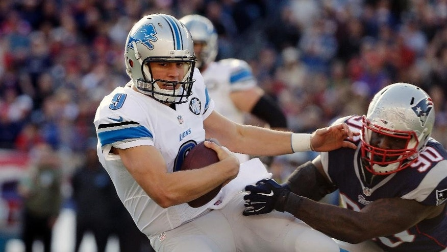 Detroit Lions quarterback Matthew Stafford (9) slips away from New England Patriots defensive end Zach Moore (90) in the first half of an NFL football game Sunday, Nov. 23, 2014, in Foxborough, Mass. (AP Photo/Steven Senne)