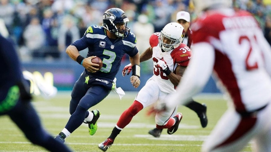 Seattle Seahawks quarterback Russell Wilson (3) scrambles for yardage as he is pursued by Arizona Cardinals strong safety Deone Bucannon (36) in the second half of an NFL football game, Sunday, Nov. 23, 2014, in Seattle. (AP Photo/Stephen Brashear)