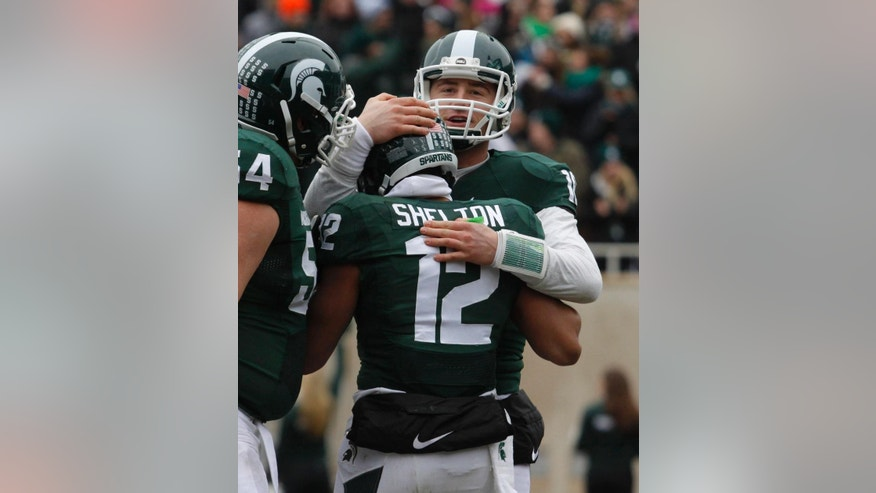 Michigan State quarterback Connor Cook, right, and receiver R.J. Shelton (12) celebrate Shelton's touchdown reception against Rutgers during the second quarter of an NCAA college football game, Saturday, Nov. 22, 2014, in East Lansing, Mich. Michigan State won 45-3. (AP Photo/Al Goldis)