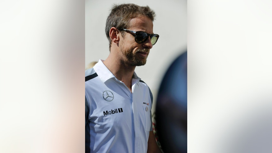 McLaren Mercedes driver Jenson Button of Britain walks in the paddock ahead of the Abu Dhabi Formula One Grand Prix at the Yas Marina racetrack in Abu Dhabi, United Arab Emirates, Sunday, Nov. 23, 2014. (AP Photo/Hassan Ammar)
