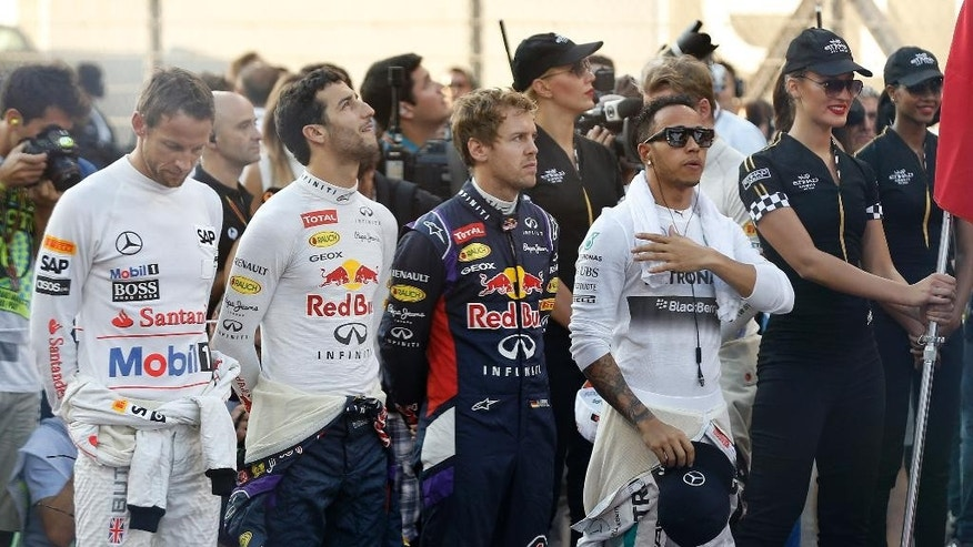 Mercedes driver Lewis Hamilton of Britain, right, stands on the grid with Red Bull driver Sebastian Vettel of Germany, Red Bull driver Daniel Ricciardo of Australia and McLaren Mercedes driver Jenson Button of Britain before the Emirates Formula One Grand Prix at the Yas Marina racetrack in Abu Dhabi, United Arab Emirates, Sunday, Nov. 23, 2014. (AP Photo/Luca Bruno)